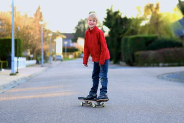 Happy boy having fun with skate board on the street