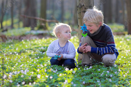 Brother and sister playing with pinwheels in spring forest