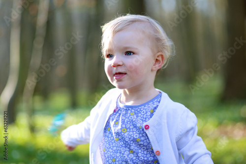 Lovely toddler girl playing in spring forest on sunny day