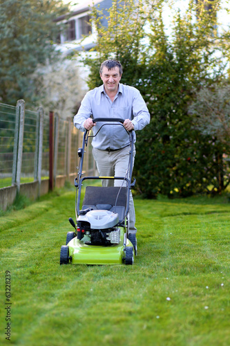 Happy man mowing the lawn in the backyard of his house
