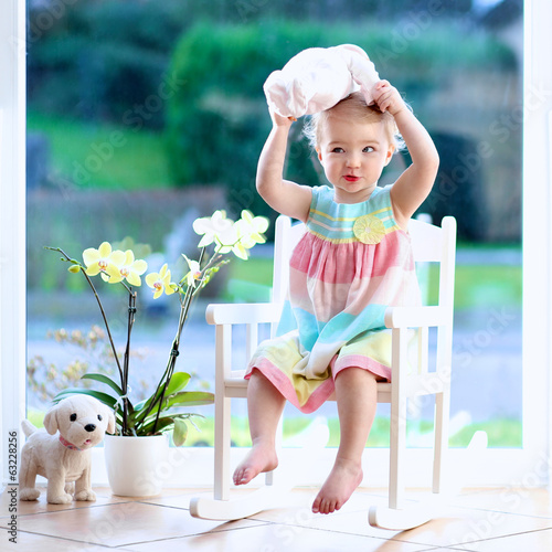 Lovely toddler girl playing with doll sitting on rocking chair
