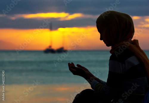 Young muslim woman praying at sunset