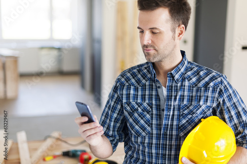 Construction worker with contemporary mobile phone