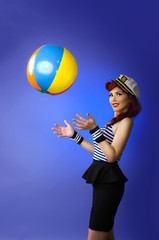 Pin up girl playing with a beach ball