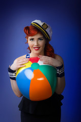 Beautiful pin up model posing with a beach ball