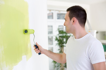 Handsome man painting wall