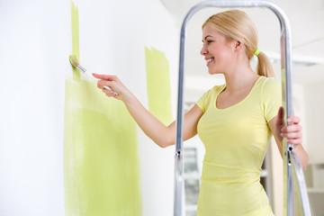 Beautiful smiling woman painting wall