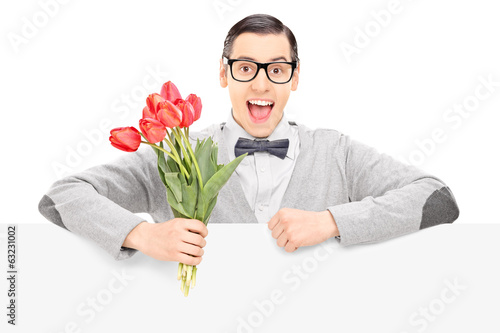 Happy male holding flowers behind a panel