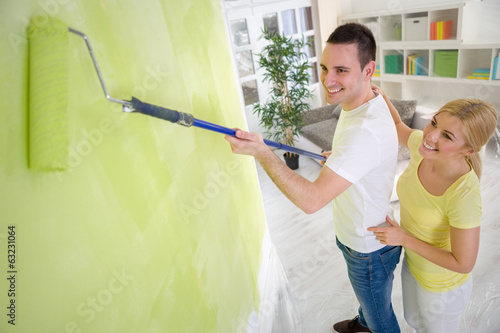 Couple painting wall with paint roller