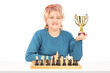 Mature female chess player holding a trophy