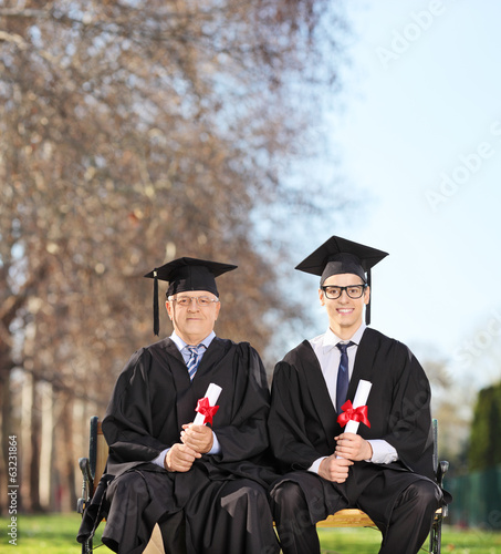 Mature and young college graduates in park