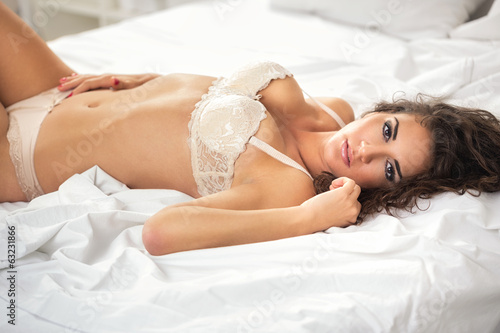 sexual girl lie on white sheet - 63231866