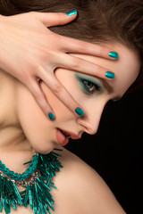 Portrait of gorgeous young woman with blue nails and eye makeup