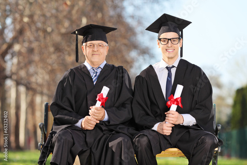 Professor and student posing on a bench outdoors