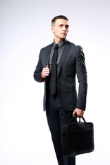 Confident businessman with bag looking away over gray background