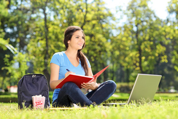 Young girl sitting on grass and writing in notebook