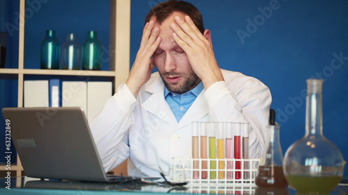 Scientist having headache during work in laboratory