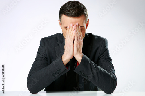 Frustrated businessman sitting at the table with hands on face