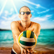 young man playing volleyball on the beach