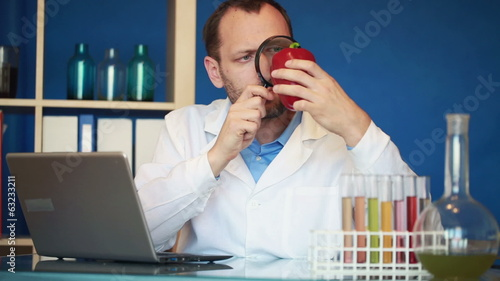 Biochemist examine red pepper, writing results on laptop