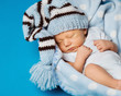 baby newborn portrait, kid sleeping in hat on blue background