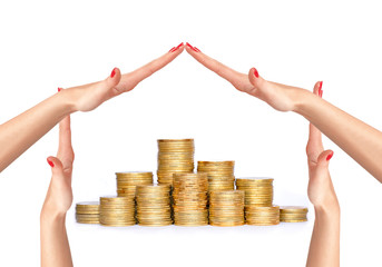 Many coins in columns and woman hands in house form isolated on