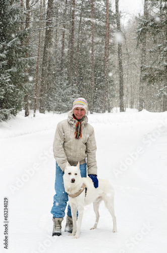 Woman with a dog on a walk in the woods during a snowfall