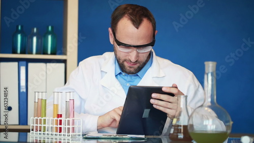 Scientist with tablet computer and test tubes in lab