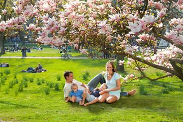 Familie im Park unter einem Magnolienbaum