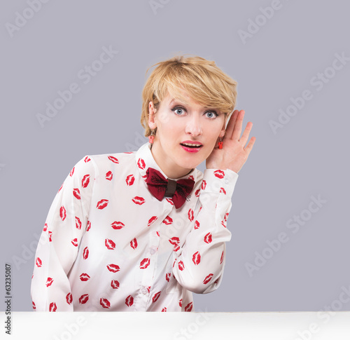 Portrait of a listening vintage style woman on gray background