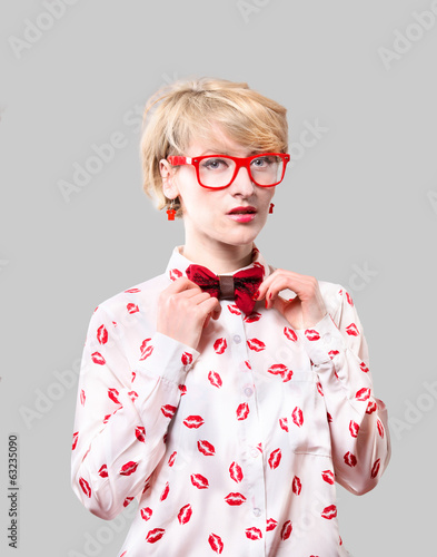 Portrait of a old fashioned blonde woman adjusting a tie