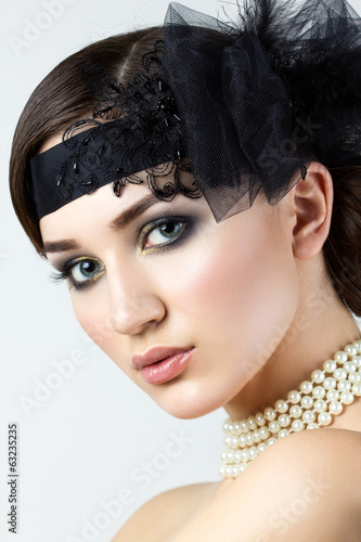Close-up portrait of retro styled woman with pearl necklace