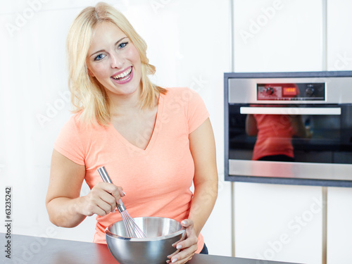 Young woman cooking in her kitchen, stiring in a pan