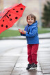 Little boy with umbrella, jumping in muddy puddles