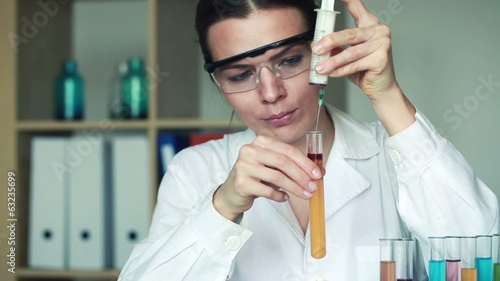 Young female chemist doing science experiment with chemicals