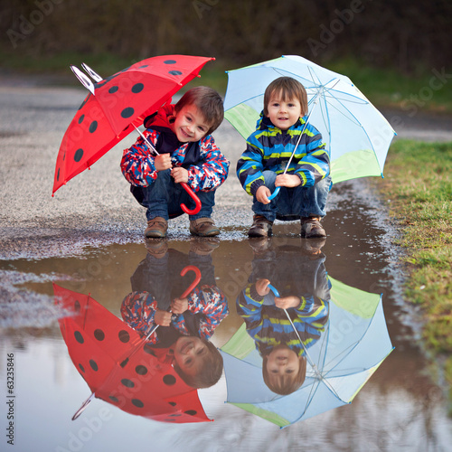 Two little boys, squat on puddle with umbrellas