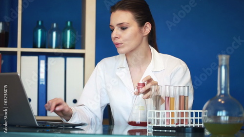 Young female chemist working with laptop and chemicals in lab