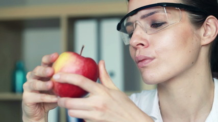 Female biochemist examine apple through magnifying glass in lab