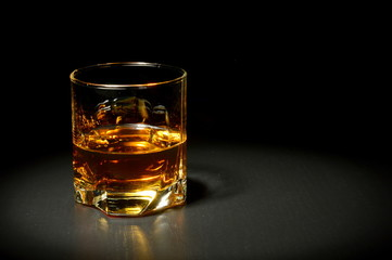 Glass of whiskey on black table