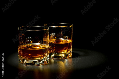 Two glasses of whiskey on black table - 63236620