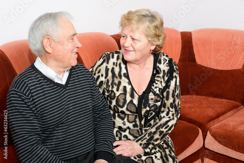Happy senior couple sitting close together on a sofa