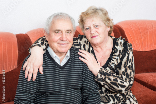 Happy senior couple sitting close together on a sofa in house