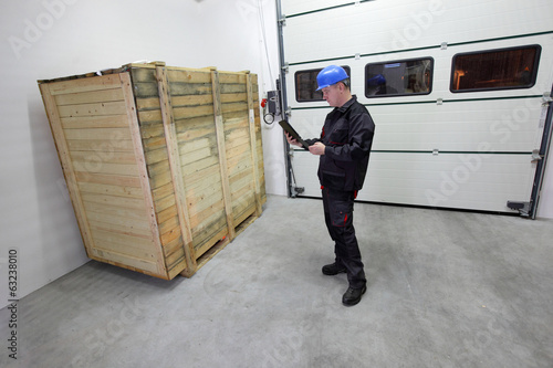 worker with tablet  checking large wooden box