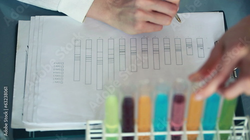 Scientist checking test tubes with chemicals and writing results