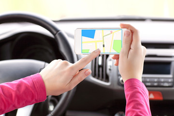 female driver hand holding a phone with interface navigator on a