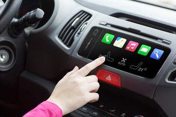 woman sitting in a car and touch play finger in a auto smart sys