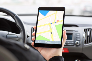 man sitting in the car and holding a tablet with interface navig