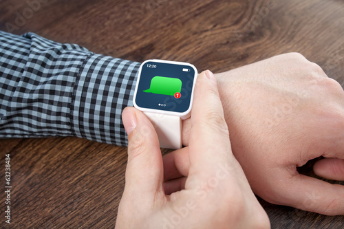 male hands with white smartwatch with message on the screen over
