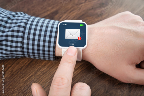 male hands with white smartwatch with email on the screen over a