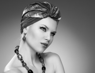 Black and white portrait of pretty woman in turban and jewelery